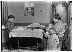 Tough: A widow and a young boy rolling papers for cigarettes in a New York tenement, 1908