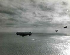 A trio of US Navy airships on convoy duty patrols above seemingly placid Atlantic waters.