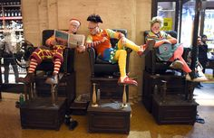 Clowns sit in the shoe-shine chairs at the Grand Central Terminal in New York