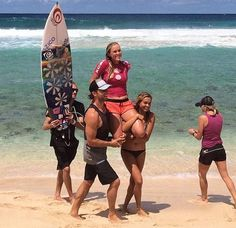 Bethany Hamilton is carried up the beach by her husband Adam and friend after winning the Surf-n-Sea Pipe Pro; photo courtesy Bethany's Face...