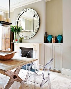 beautiful large round mirror over the mantle + ghost chairs in a modern-rustic dining space