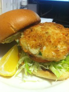 Walleye cake sandwich.   Shredded lettuce, tomato, lemon tartar on buttered egg bun.