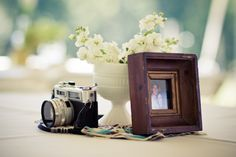 Maybe old cameras as part of your centerpieces?  I bet I can find them cheap in thrift stores up here.  Adds a nice personal detail for your interests. Also, if you can find film for them, you could get some interesting wedding photos.