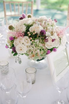 Centerpiece with various color roses, pink astilbe, hypericum berry, scabiosa pod and lambs ear.
