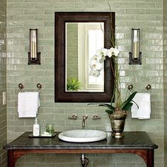 The Powder Room - This space is stunning with its interesting mix of textures including walls of glazed moss green tile (annsacks.com), a Carrara marble vessel sink (us.kohler.com), a granite vanity top (artisan-counters.com), aged iron sconces circalighting.com), and a faux-shagreen mirror (madegoods.com).