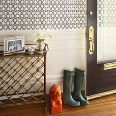 source: Anyon Interior Design    Cole & Sons David Hicks Hexagon Wallpaper, brass console table, black door with brass hardware and orange foo dog.