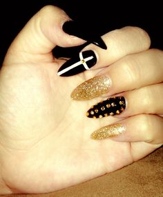 Acrylic Nails with black,glitter gold Gel polish & Pointed tip. Gold Rhinestone & White Cross design. You like? Done at Cool Nails in Cerritos.