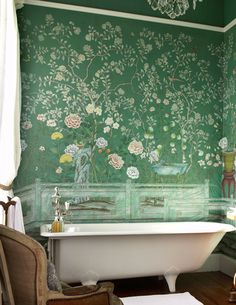 Teal chinoiserie wallpaper and white claw foot tub in a traditional bathroom
