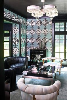 Living room with patterned wallpaper and coordinating bold furniture.