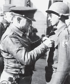 """Lt. Gen. Truscott decorates a lieutenant of the Brazilian Expeditionary Force. The patch worn by the Lt. evoked the """"smoking cobra"""" nickname that the BEF took for itself, repurposing the rumor in Brazil, prior to her declaration of war, that Hitler had said it """"more likely for a snake to start smoking than for Brazil to join the war"""". Although officially sanctioned, most of the patches were produced in Italy by local craftsmen."""