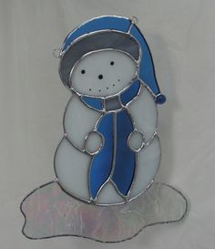 He is SO cute! I was tempted to keep him for my collection! Made of wispy white glass, with his hat and scarf being blue and grey. The tip of his hat is sporting a glass nugget. He is standing on a large section of Iced iridized clear glass. Facial features are painted on.  Hes a substantial 9.5 tall by 7 wide at the base. Comes with suction cup for hanging.   ♥ Any overcharges on shipping would be refunded to you.  I offer free gift wrapping, send me a note!   ~*~ Click here to go to my…
