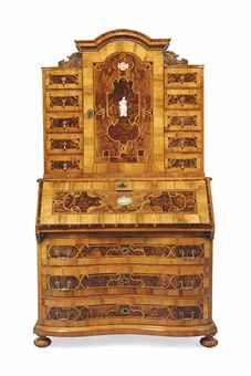 A GERMAN WALNUT, FIGURED WALNUT, ASH, FRUITWOOD & EBONY BUREAU CABINET MID-18TH CENTURY, PROBABLY BRUNSWICK Banded & crossbanded overall & bone inlaid with figures & flowerbaskets surrounded by interlaced strapwork, the moulded arched cornice above a central cupboard door, flanked by five drawers to each side, above a hinged slope, above three further drawers, on bun feet 80 in. high x 43½ in. wide x 23½ in. deep
