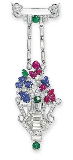 AN ART DECO DIAMOND, SAPPHIRE, RUBY AND EMERALD PENDANT BROOCH Designed as a circular and baguette-cut diamond vase set with a hexagonal-cut diamond, extending circular-cut diamond branches with carved cabochon sapphire, ruby and emerald leaves, from two baguette-cut diamond chains, to the circular and baguette-cut diamond surmount accented with a cabochon emerald, mounted in platinum, circa 1925