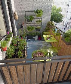 Un balcon en ville qui n'a rien à envier à un jardin. Des jardinières suspendues accueillent fleurs et aromates et transforment le balcon  d'appartement en un véritable espace vert.