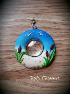 You can almost hear the waves lapping the shore, and the wind whistling through the cattails.... Handcrafted in polymer clay, with a center glass