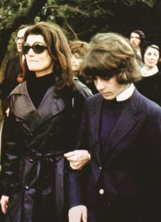 Jackie Kennedy Onassis took her son's arm as they proceeded towards the chapel funeral of her husband and his stepfather Ari, May 21, 1975.