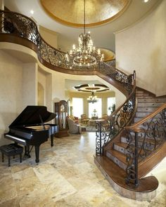 Mediterranean Staircase.... 3 elements I LOVE in an entry:  Grand or baby grand piano,  curved stair well, and chandelier :)