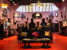 """Anna Sui Soho Store...""""Lavender walls, stained red floors, Victorian Bombe' furniture painted glossy black with purple velvet upholstery, rock posters, wicker butterflies, Aubrey Beardsley prints, decoupage dolly heads..."""""""