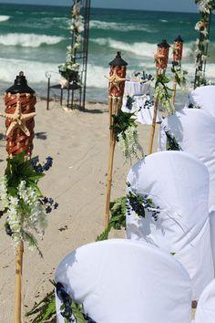 Tiki torches as aisle decor for beach wedding