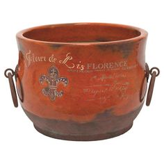 Celebrate Tuscan charm in your living room or entryway with this eye-catching terracotta planter, showcasing an orange finish and a typographic motif.