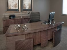 This custom built desk features a unique wood finish, shape, and custom details that make it super functional