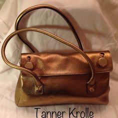 "TANNER KROLLE Sam Brown Leather Bag in Gold JUST REDUCEDTanner Krolle's classic Sam Brown shoulder bag in gold. TK is known for great craftsmanship & this bag is no exception. Pebbled caviar gold leather & black suede lining. Fold over top. 2 button closures w/logo stamp (you have to button to close). 2 handles 24""L & 8"" drop. 1 main compartment. Inside: zipper pocket, cell phone pocket, TK logo tag & key fob. 4 gold tone protective feet. Made in Italy. 12""W x 8.5""H x 3""D. In excellent…"