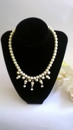 This elegant pearl and crystal drop necklace will add elegance to any outfit. It is handcrafted with Swarovski crystals, premium, lustrous, glass pearls, silver plated beads, and a silver plated lobster clasp. It also has a 2 inch, pearl embellished extender chain.  Length: approximately 16 inches, not including the 2 inch extender chain  Pearl drop length: ranges from approximately 1/4 inch, to 1 1/2 inches in the center  Colours: light cream(shown above), white, soft pink, sage gr...