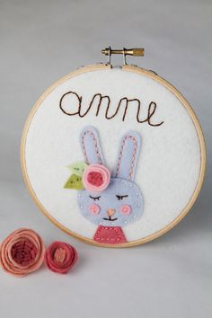 This felt bunny nursery name sign features your little girls hand-stitched in a whimsical handwritten font. This unique 3D name sign is sure to inspire and delight your child.  What does the Bunny Say? Your favorite persons name, of course!  Your daughter will be delighted to see her name in stitches on this adorable name sign.  A double layered rose is tucked behind the bunnys ear. She is accessorized and dressed up (in rose pink top)!  She has pink cheeks of felt. Her nose, mouth and eyes…