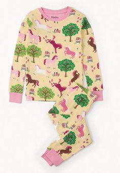 2-delige meisjes pyjama Pony orchard van het kinderkleding merk Hatley. Een pyjama uit 2 delen met een gele t-shirt. De t-shirt heeft een all over print van verschillende kleuren pony's, met boompjes en appels erbij. De ronde hals en de uiteinde van de mouw is afgewerkt in het licht roos.  De pyjama broek heeft een gele kleur, en is voorzien van een all over print idem als de t-shirt.