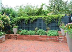 Beautiful fence and brick raised beds.