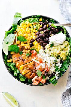 Chicken Burrito Bowls made with taco-seasoned chicken, cilantro-lime rice, salsa, guacamole, corn, beans, and a delicious creamy cilantro sauce.