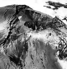 Mount St. Helens' summit after several small explosive eruptions opened pit craters. The smaller of the two pit craters was formed first on March 27, 1980. Subsequent eruptions opened the farther crater. The two craters subsequently merged. View looking west.
