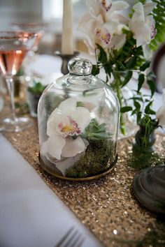 Pale copper sequin table runner with orchids and bell jars as minimalist wedding table decor