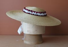 The straw hat:  mine has red pleated grosgrain ribbon and grosgrain ties.