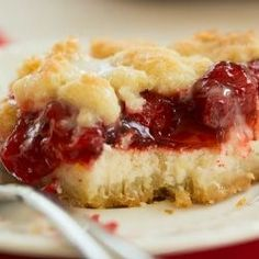 Layers of cheesecake filling and cherry pie filling are sandwiched between a crumb crust and topping.