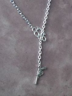 Up for bids is this Silver Brass Knuckle Duster & Revolver Gun Pendant on silver Chain. It is a Lariat Artisan Necklace. Knuckle and gun charms are tibetan silver in color and knuckle charm is approxi
