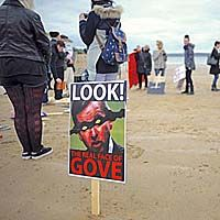 The Art Party with Gove placard on the beach