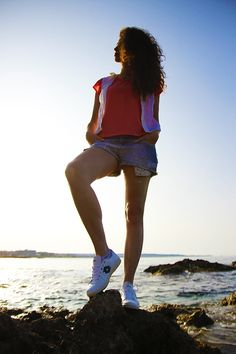 Walking over the sea, vest, denim shorts and sneakers