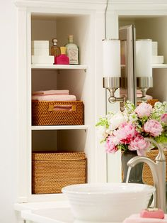 love this built in shelf with pretty baskets for the bathroom. Also love the sink and all the white.