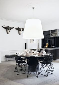 Elegant and modern kitchen and dining area with a round and black dining table surrounded by black chairs from Moooi.