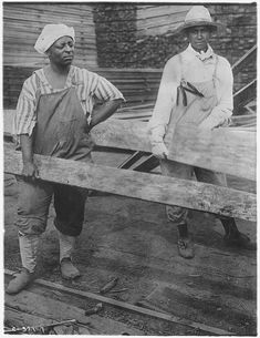 Women at Work in Lumber Yards. [African-American] Women, Dressed in Mens Clothes, Lifting Heavy Pieces of Lumber.  1919, photo by YWCA