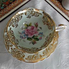 A vintage Paragon cup and saucer done in a pale mint green with a pink rose in centers and a gold floral scroll on edge.  Marked as shown on bottoms