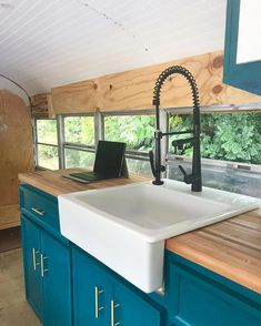 This kitchen features an apron sink, butcher block counters, teal cabinets, and metal hardware. Tiny House Movement // Tiny Living // Tiny House on Wheels // Skoolie // School Bus Conversion // Tiny Home // Architecture // Home Decor Teal Cabinets, Metal Kitchen Cabinets, Teal Kitchen, Built In Cabinets, Painting Kitchen Cabinets, Kitchen Decor, Kitchen Sink, Kitchen Counters, Country Kitchen