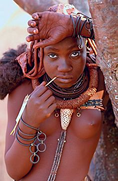 Himba , Angola.  She wears a valuable Conus Marmoreus ( 'Marble Cone' ) traded from east Africa.