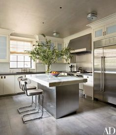 The kitchen is appointed with a BlueStar range, a Sub-Zero refrigerator, and sink fittings by Michael S. Smith for Kallista; the stools are by York Street Studio, and the flooring is by Porcelanosa.