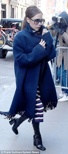 In Vogue: The designer got changed into a stripey dress and oversized navy coat, similar to the ones shown on the catwalk