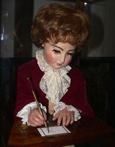 """El ponente es otro de los autómatas de Jaquet-Droz, que podría producir cuatro imágenes diferentes: retratos de Luis XV, de María Antonieta y de Luis XVI, que eran la familia real, y un perro con la leyenda Mon toutou (""""mi perro"""") escrita junto a él, y Cupido manjando un carro arrastrado por una mariposa. El niño también se mueve en su silla, y en ocasiones sopla el lápiz para quitarle el polvo."""