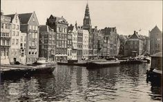 1940's. View on Damrak in Amsterdam. On the left the back-side of the warehouses on the Warmoesstraat. On the right, partially visible, the Beurs van Berlage. On the left the tower of the Oudekerk. Photo Gebroeders Spanjersberg. The Damrak is an avenue and partially filled in canal. It is located between Centraal Station and Dam square and is the main street where people who have arrived in Amsterdam by train enter the city. #amsterdam #1940 #Damrak