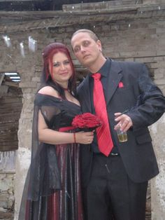 photo of gothic bride and groom with red wedding bouquet
