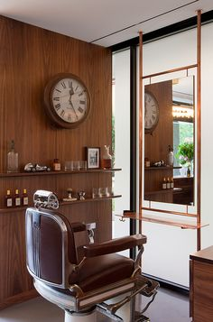 Barber's salon. Vintage barber chair. Walnut cabinetry and wall cladding. Copper furniture. Old train station clock. Kate Challis Interiors.